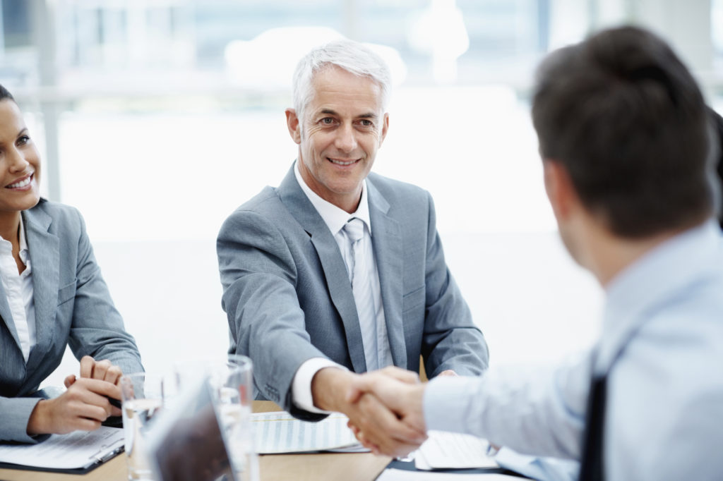 Businessmen Shaking Hands In A Group Setting